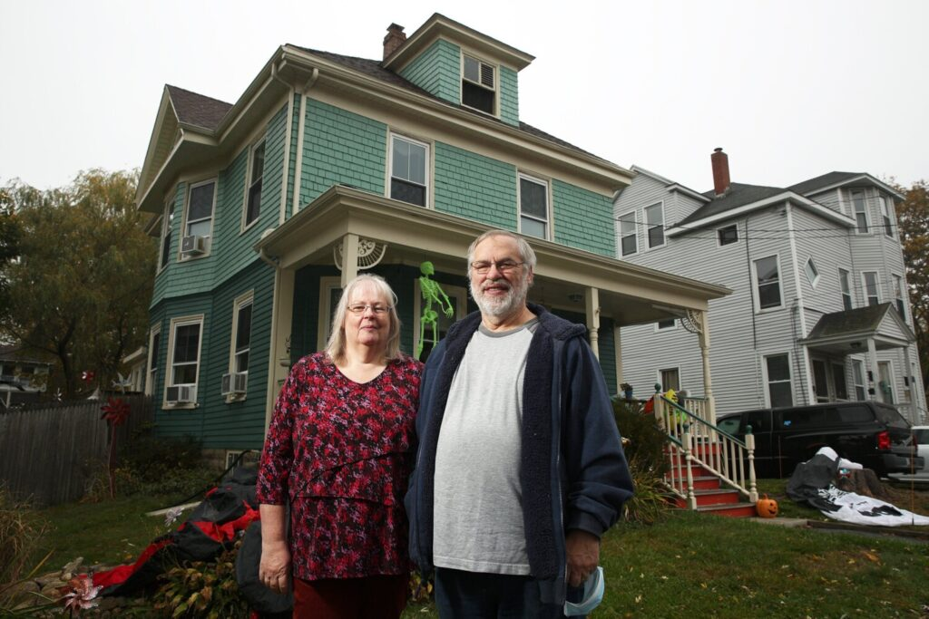 Charlie and Cheryl Wallace, standing in front of their house in Portland on Wednesday, will be at home a lot this winter and will benefit from low heating oil prices, as will thousands of other Mainers.