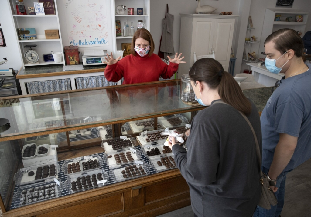 Bath Sweet Shoppe owner Jennifer DeChant helps customers Karen and Richard Andrews of Southbury, Connecticut, at the store on Oct. 22. DeChant is one of hundreds of Mainers that have acquired or launched their own business ventures since the coronavirus pandemic began.