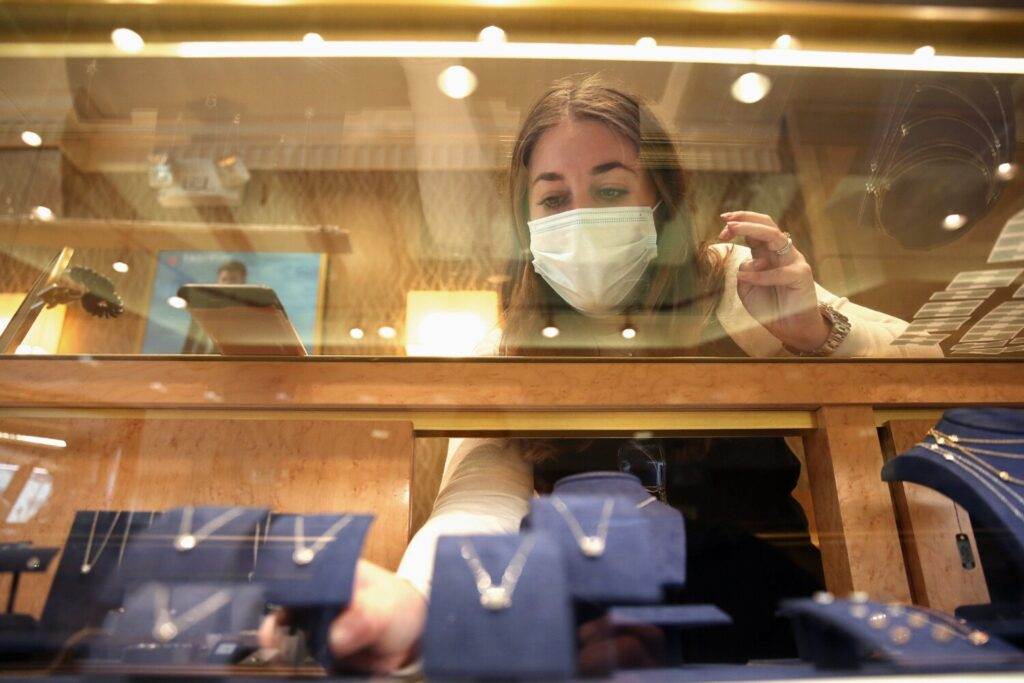 Kelly Hersom, salesperson at Springer's Jewelers on Congress Street in Portland, affixes new price stickers to necklaces in a case on Thursday. The store is marking its 150th anniversary this year.