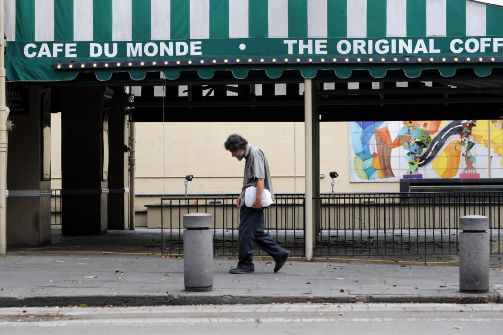 A man walks past the closed Cafe Du Monde  in the French Quarter of New Orleans. A Federal Reserve board member warned last week that the economy's most severe risks are the lack of further stimulus and the persistent viral outbreak.