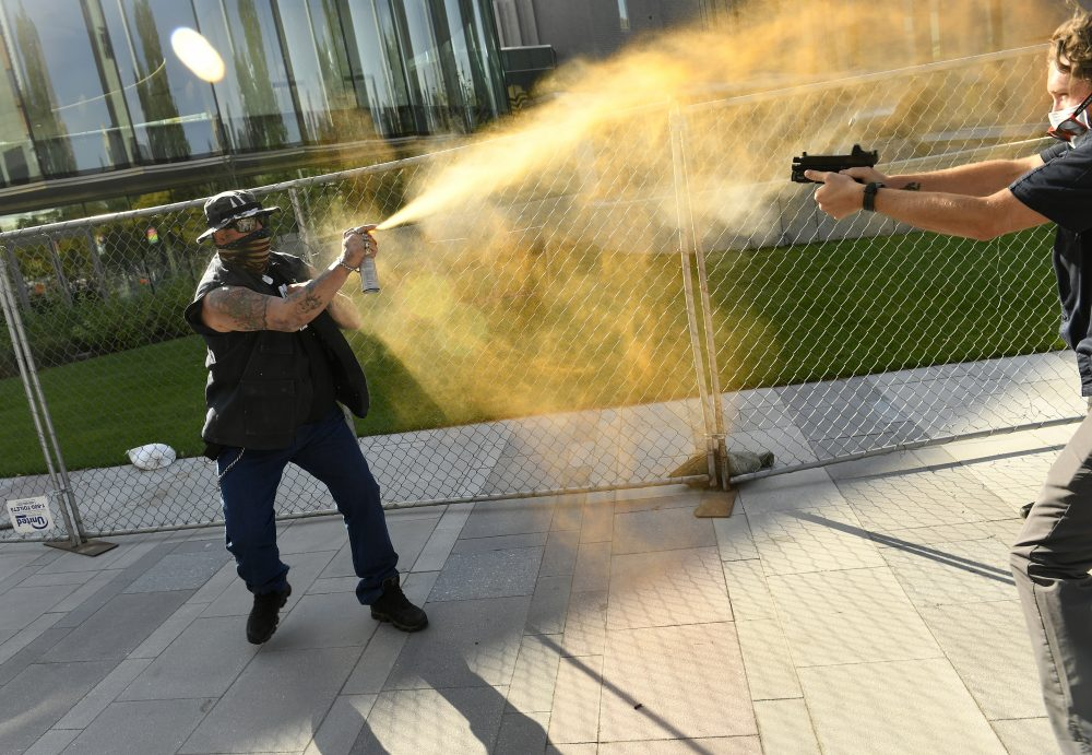 A man sprays Mace, left, at a security guard on Saturday in Denver. A private security guard working for a TV station was in custody Saturday after a person died from a shooting that took place during dueling protests in downtown Denver, the Denver Post reported.