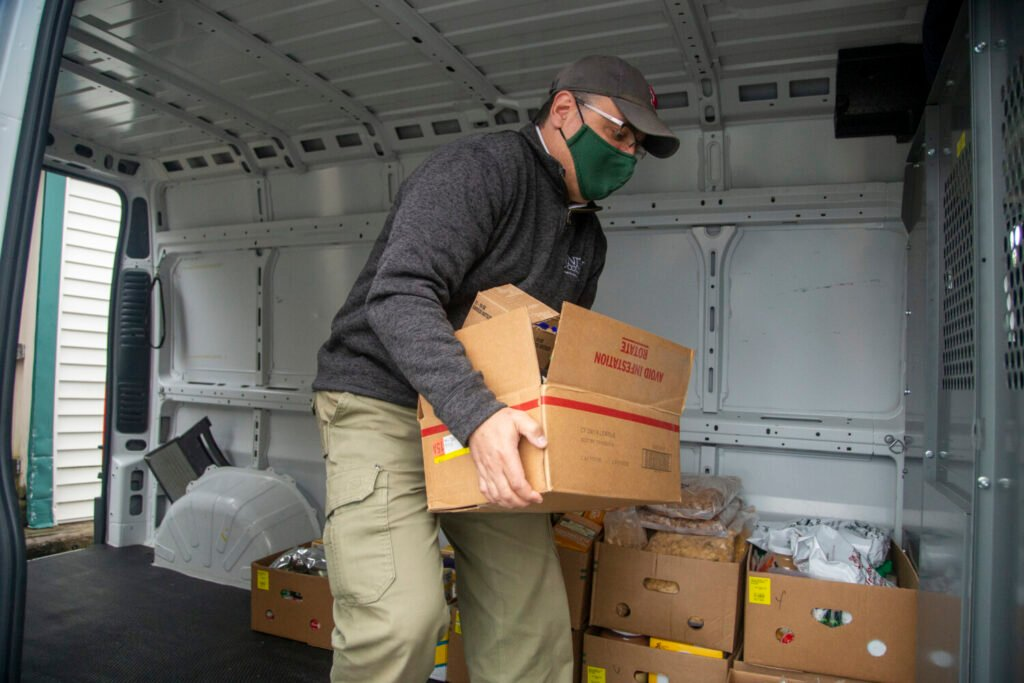 Dr. Melik Peter Khoury, president of Unity College, helps load food into the Waterville Food Bank's van on Oct. 21. The college donated 1,141 individual items and roughly 1,851 pounds.