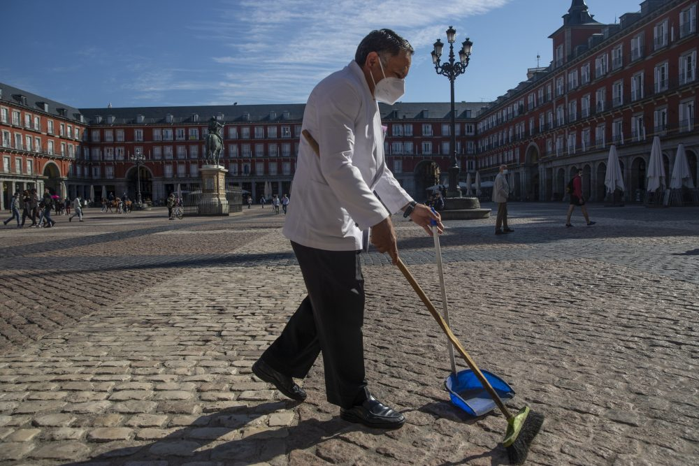 A waiter sweeps the terrace of a bar Oct. 9 in downtown Madrid, Spain.