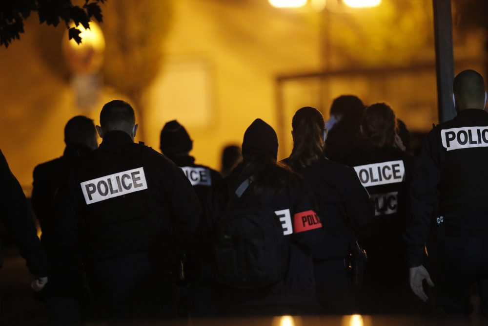 French police officers gather outside a high school after a history teacher who opened a discussion with students on caricatures of Islam's prophet Muhammad was beheaded Friday  in Conflans-Saint-Honorine, north of Paris. Police fataly shot the suspected killer.