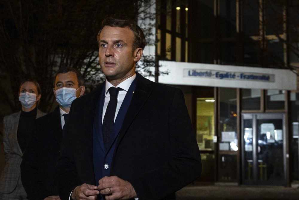 French President Emmanuel Macron, with French Interior Minister Gerald Darmanin, speaks in front of a high school Friday in Conflans Sainte-Honorine, northwest of Paris, after a history teacher was beheaded. He urged the nation to stand united against extremism.