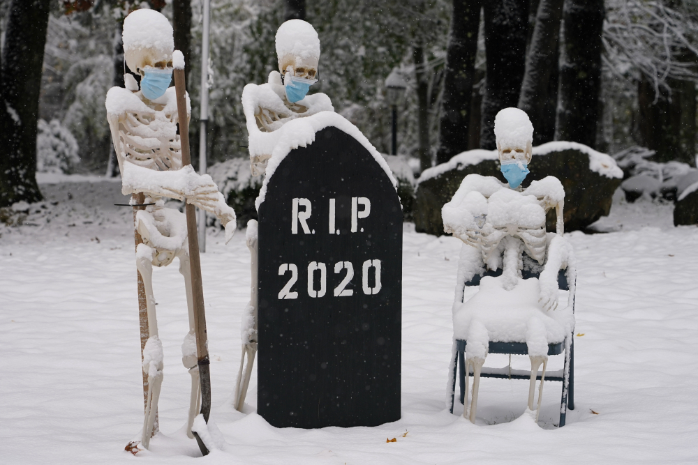 Snow falls on masked skeletons ready to bury the year 2020 on Friday in North Andover, Mass.