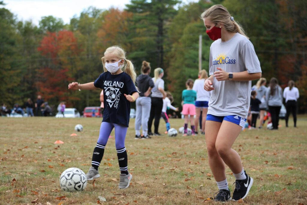 First grader Raegan Marston shares her dribbling skills with Lady Eagles soccer player Katie True at ShineOn Saturday, an annual event to link local girls with the Messalonskee girls soccer players for a day of mentorship in honor of Cassidy Charette.