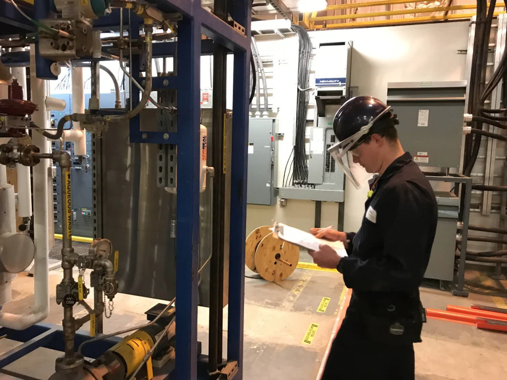 A technician takes a reading from an apparatus that turns wood waste into biofuel in this 2017 photo of Biofine's test facility in Old Town. The company plans to open another facility in Maine to produce its zero-emission heating oil on a commercial scale.