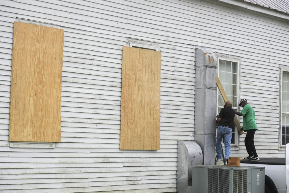 The Rev. Ivory Williams Sr. and Chris Welch board up the windows of St. John Baptist Church while preparing for Hurricane Delta on Thursday in Charenton, La.