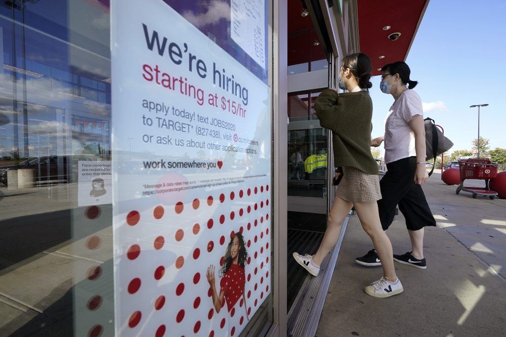 Passers-by walk past a hiring sign as they enter a Target retail store location, Wednesday in Westwood, Mass. The number of Americans seeking unemployment benefits declined last week to a still-high 837,000, evidence that the economy is struggling to sustain a tentative recovery that began this summer.