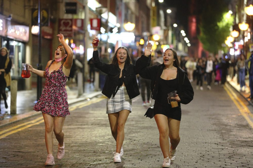 People socialize in Liverpool city centre, ahead of the 10 p.m. curfew that pubs and restaurants are subject to in order to combat the rise in coronavirus cases in England, Saturday.