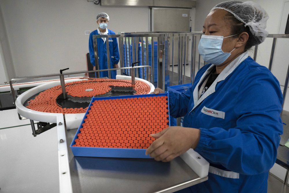 A worker feeds vials for production of SARS CoV-2 Vaccine for COVID-19 at the SinoVac vaccine factory in Beijing last month. China said on Friday that it is joining the COVID-19 vaccine alliance known as COVAX.