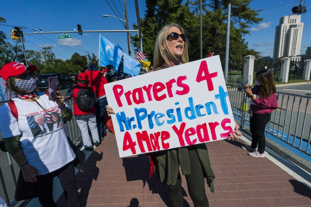 Karen Simon from the District of Columbia joins other supporters of President Trump outside the Walter Reed National Military Medical Center in Bethesda, Md., on Monday before he was released.