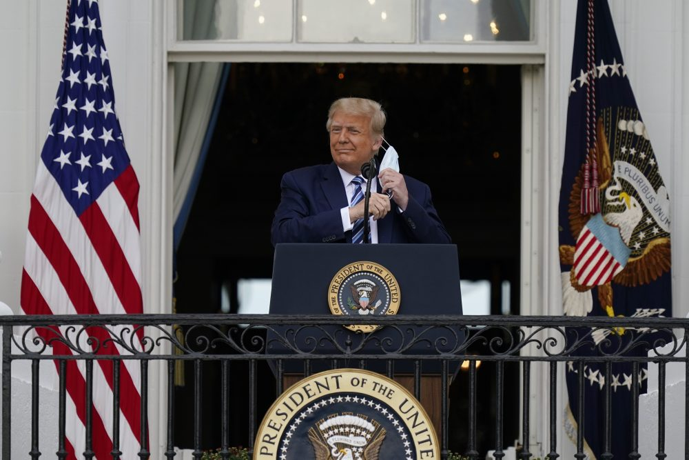 President Trump removes his face mask to speak from the Blue Room Balcony of the White House to a crowd of supporters on Saturday in Washington.