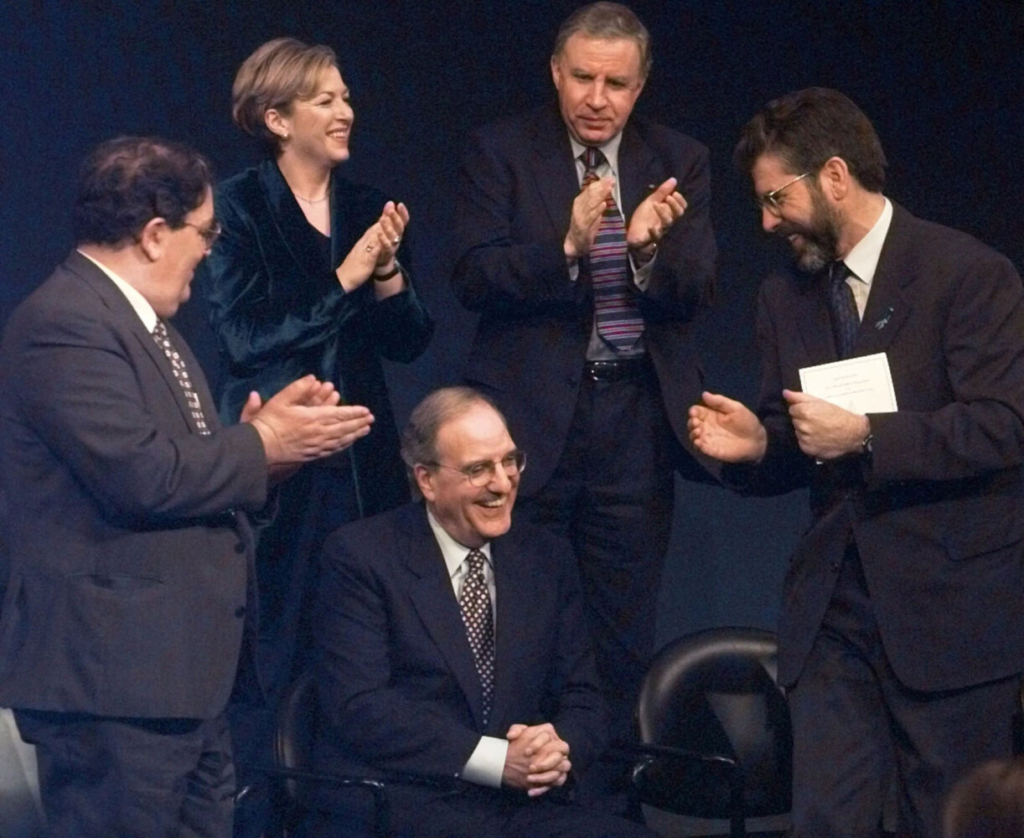 Former U.S. Senator and Chairman of the Northern Ireland Peace Talks, George Mitchell, center, smiles as he is applauded by fellow recipients of the John F. Kennedy Profile in Courage Award, John Hume, left, of the Social Democratic and Labour Party and Gerry Adams, right, of Sein Fein during a ceremony in Boston, in 1998.  In all, eight political leaders of Northern Ireland and Mitchell received the award in recognition of their negotiation of the Good Friday Peace Agreement.