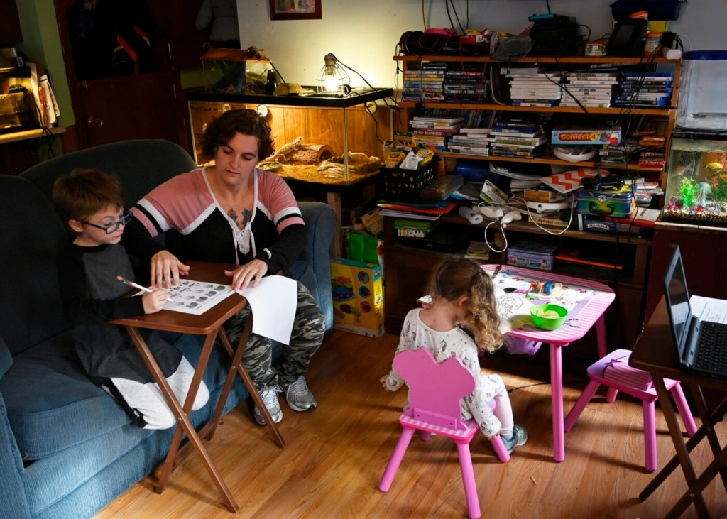 Ashley Whitman helps her son Blake with his homework as her daughter Bella colors at their Winslow home on Thursday.  Whitman had her hours as a preschool teacher cut back, and she can't find a job that fits her schedule as she cares for her three children during the coronavirus pandemic.