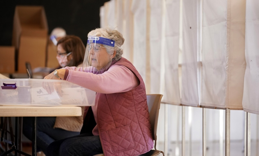 Becky Beers reads names on absentee ballot envelopes as another election worker verifies them on a list at Kennebunk Town Hall on Saturday.