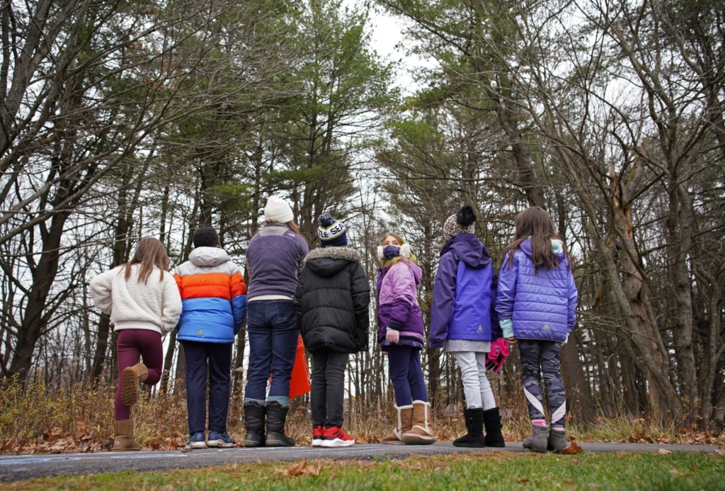 Katie West, a teacher at Lyseth Elementary in Portland, and a class of third-graders examine aspects of trees before starting to paint them during an outdoor art class in the woods last Nov. 13.
