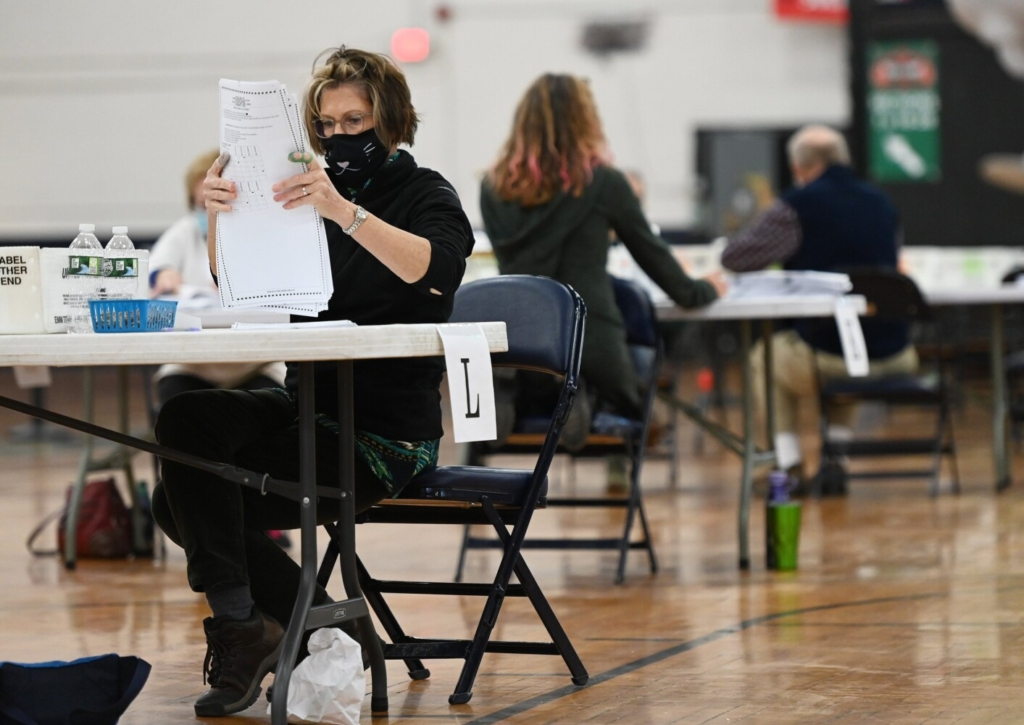 Betsy Reardon goes through ballots during the recount of the referendum question E at the Portland Expo on Thursday.