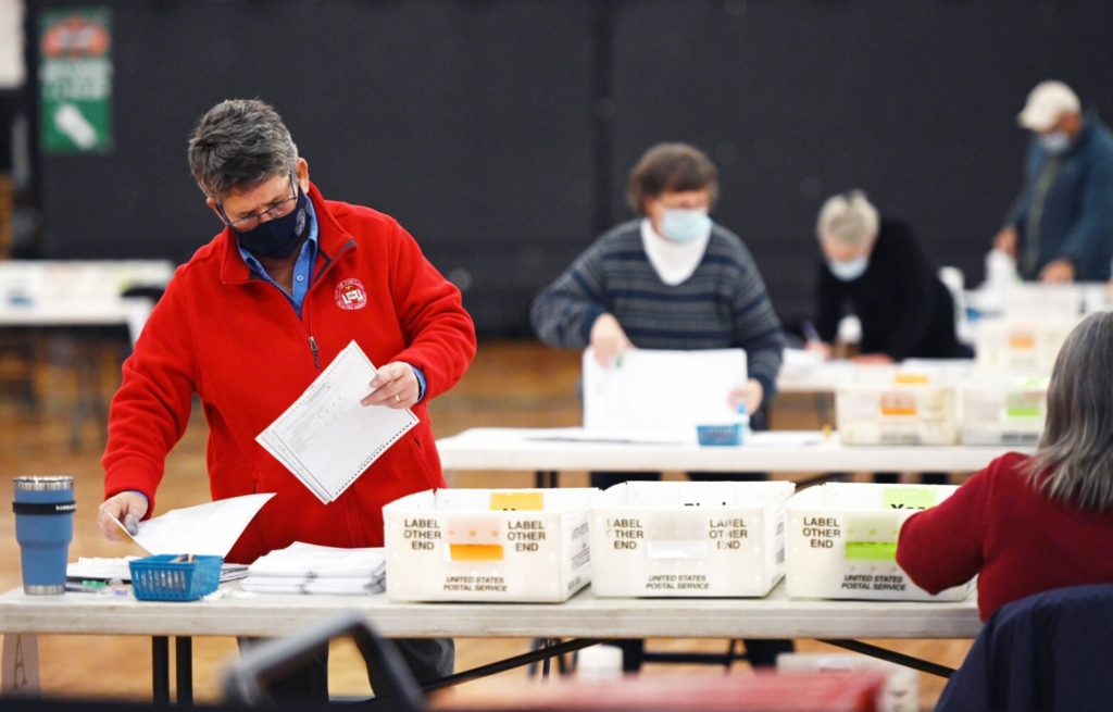 Kathy Alves, left, and others go through ballots during the recount process of referendum question E at the Portland Expo on Thursday.