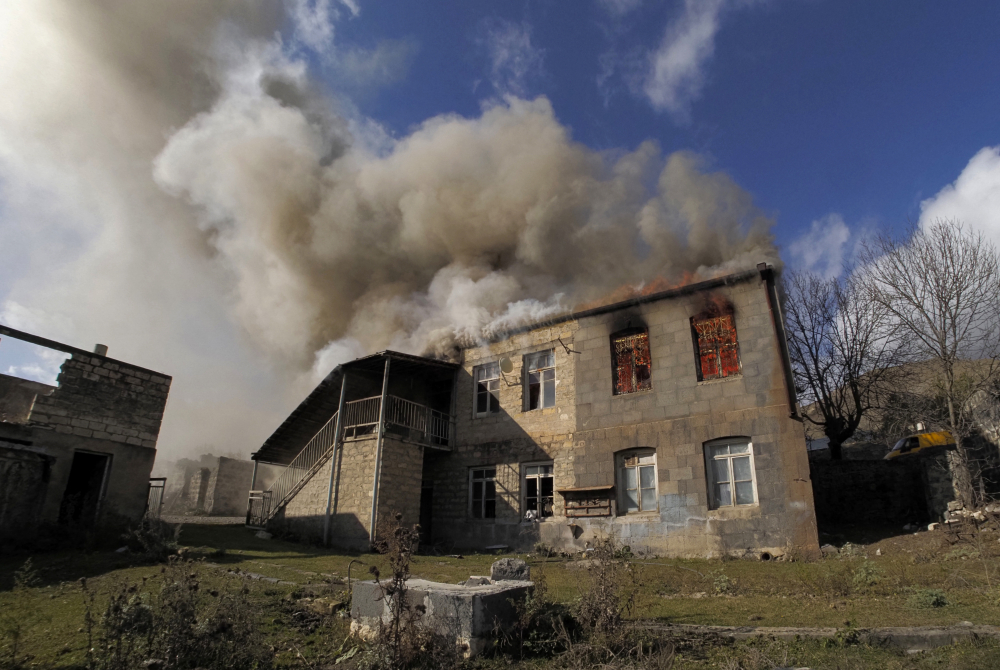 Smoke rises from a burning house in an area once occupied by Armenian forces but soon to be turned over to Azerbaijan, in Karvachar, the separatist region of Nagorno-Karabakh, on Friday.