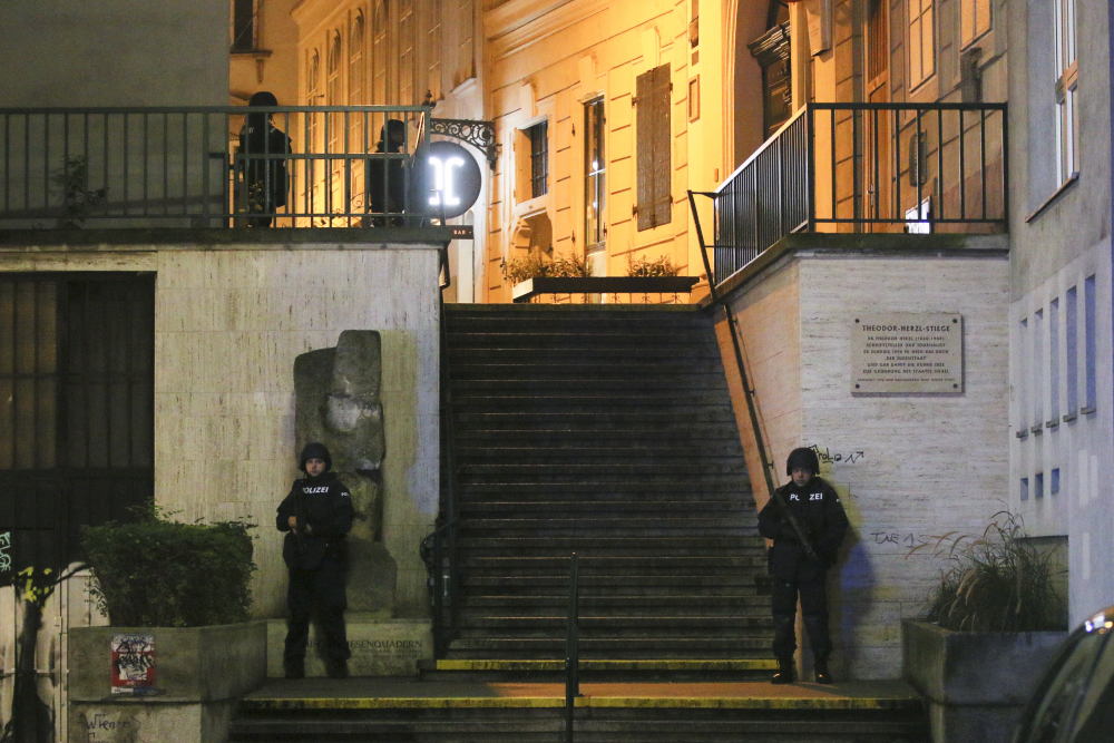 Police officers stay in position near a synagogue after an attack in Vienna killed two people.