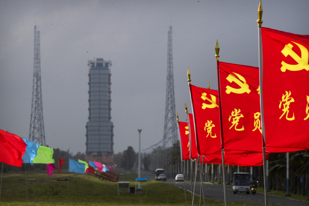 Flags with the logo of the Communist Party of China fly in the breeze near a launch pad in Wenchang on Monday.