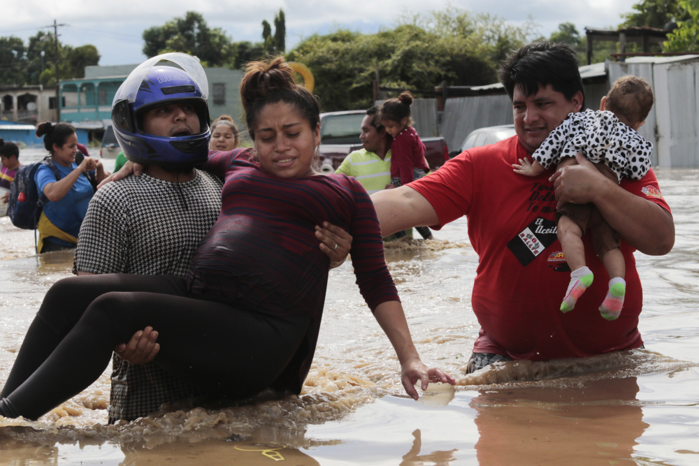 A pregnant woman is carried out of an area flooded by water brought by Hurricane Eta in Planeta, Honduras, on Thursday. The storm that hit Nicaragua as a Category 4 hurricane on Tuesday had become more of a vast tropical rainstorm, but it was advancing so slowly and dumping so much rain that much of Central America remained on high alert.