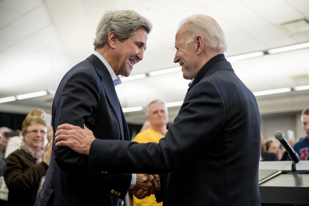 Democratic presidential candidate former Vice President Joe Biden smiles as former Secretary of State John Kerry, left, takes the podium to speak at a campaign stop Feb. 1 at the South Slope Community Center in North Liberty, Iowa.