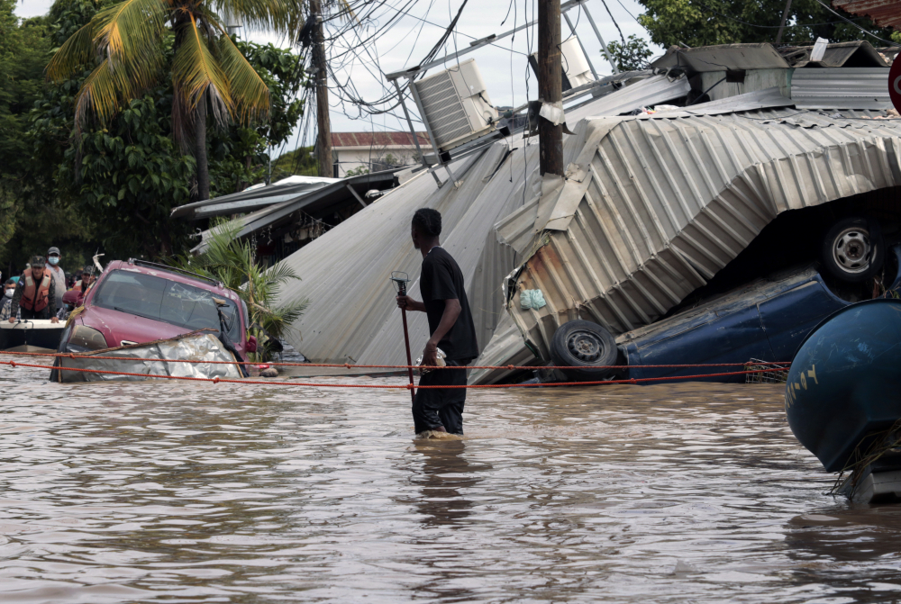 A resident walking through a flooded street looks back at storm damage caused by Hurricane Eta in Planeta, Honduras, earlier this month. Honduras' Red Cross was just finishing up its search and rescue phase after Hurricane Eta when Iota hit.