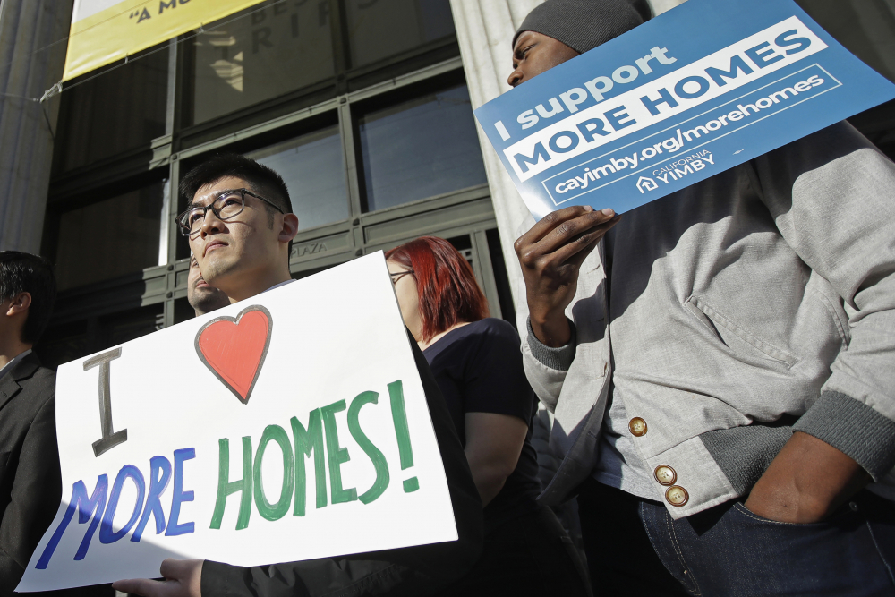 Men hold up signs at a rally outside of City Hall in Oakland, Calif., in January 2020. The Biden administration is expected to embrace policies aimed at stemming evictions and stabilizing housing for renters.
