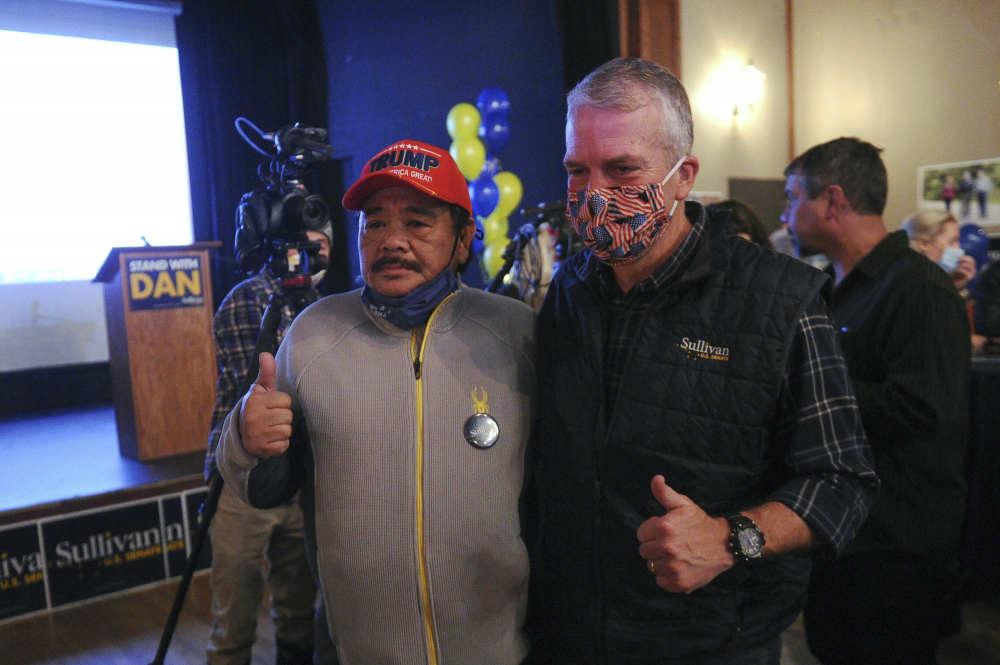 Sen. Dan Sullivan, R-Alaska, right, poses for a photograph with supporter Rolando Torralba at a campaign party this month in Anchorage, Alaska.