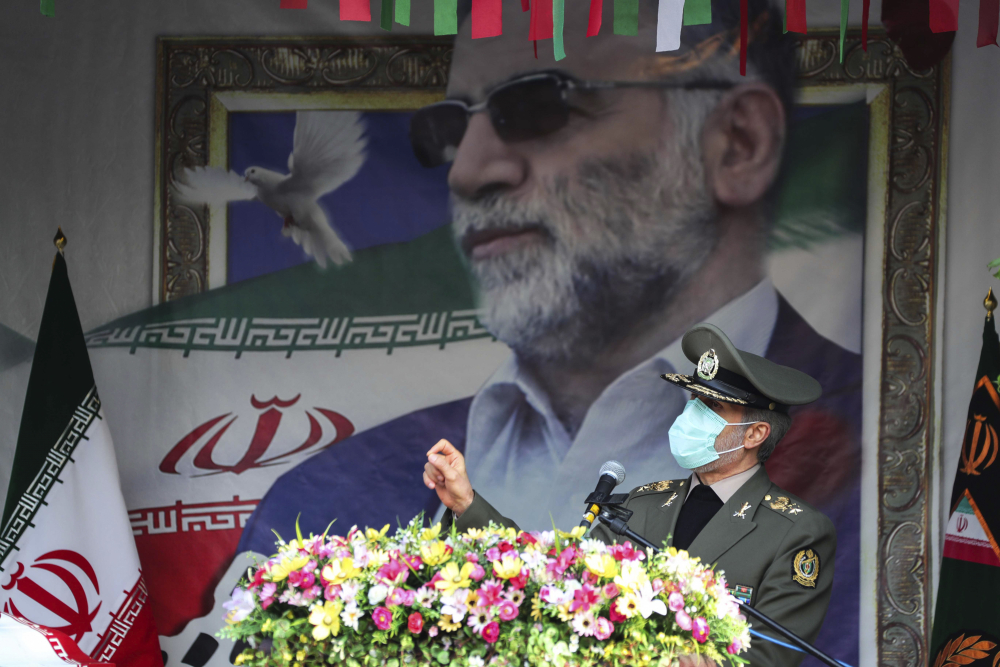 """In this photo released by the official website of the Iranian Defense Ministry, Defense Minister Gen. Amir Hatami speaks during a funeral ceremony for Mohsen Fakhrizadeh, a scientist who was killed on Friday, shown in the banner at background, in Tehran, Iran, Monday, Nov. 30, 2020. Iran held the funeral Monday for the slain scientist who founded its military nuclear program two decades ago, with the Islamic Republic's defense minister vowing to continue the man's work """"with more speed and more power."""" (Iranian Defense Ministry via AP)"""