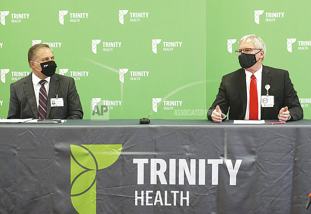 Dr. Jeffrey Sather, chief of staff, right, speaks at a news conference at Trinity Health on Oct. 9 with Randy Schwan, Trinity vice president in Minot, N.D.  Local hospital workers are becoming overwhelmed as COVID-19 cases in the Minot area have risen significantly in recent weeks.