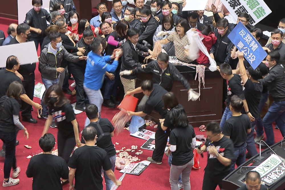 """Lawmakers fight during a parliament session in Taipei, Taiwan, Friday , over a soon-to-be-enacted policy that would allow imports of U.S. pork and beef. A blue banner at right reads: """"Protest against ractopamine pork, We want a referendum."""" (FTV via AP)"""