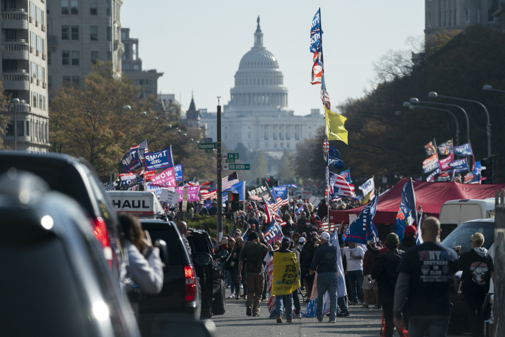 A motorcade carrying President Trump drives by a group of supporters holding a rally near the White House on Saturday.