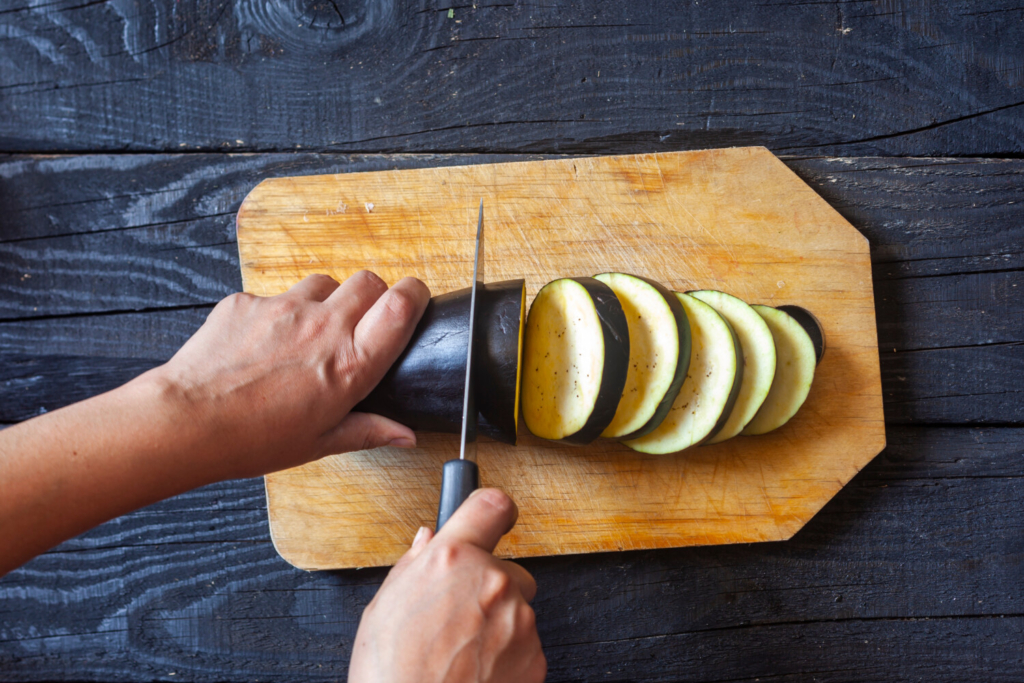 To make Personal Pantry Eggplant Parm, begin by cutting three eggplants into rounds.