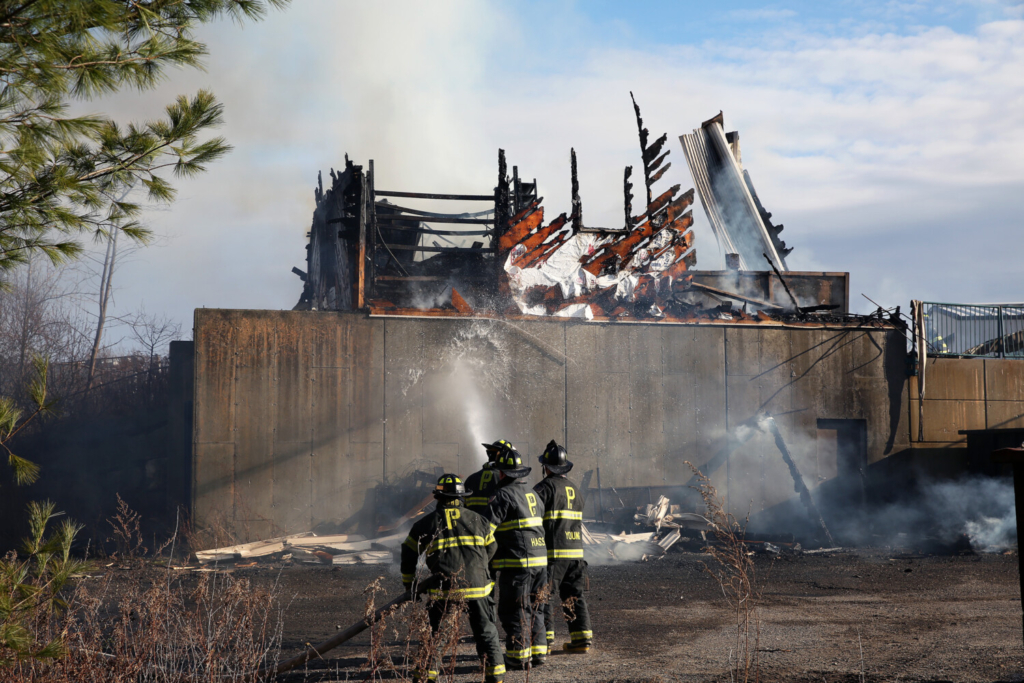 Firefighters extinguish a blaze in a structure that houses a trash compactor at the Peaks Island transfer station on Friday.