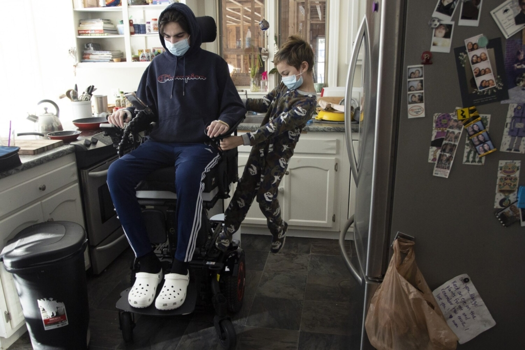 At home in Maine, Jack  Weeks takes his brother, Gus, 9, for a ride on his wheelchair.