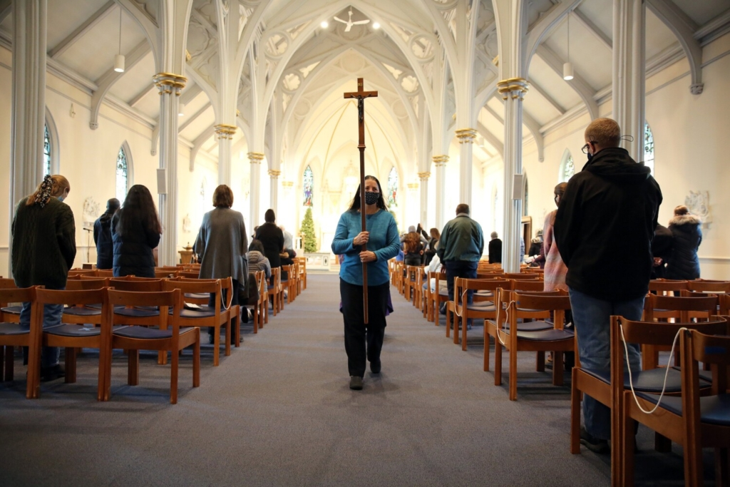 Churchgoers are socially distanced at Cathedral of the Immaculate Conception in Portland as church sacristan Dianne Tardy carries the cross at the end of daily Mass on Wednesday.