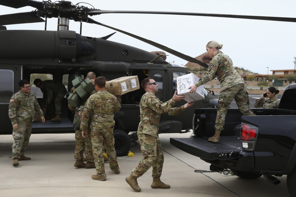 Members of an Arizona National Guard load a helicopter with medical supplies to be taken to the remote Navajo Nation town of Kayenta in April. Tribal members are working to protect elders by delivering meals and protective gear so they can remain safe at home.
