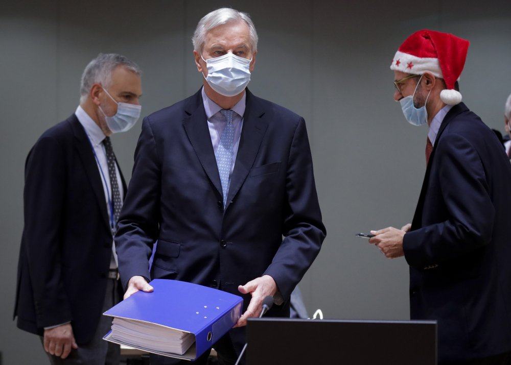 European Union chief negotiator Michel Barnier, center, carries a binder of the Brexit trade deal during a special meeting of Coreper at the European Council building in Brussels on Friday. After the deal was announced on Thursday, EU nations already showed support for the outcome and it was expected that they would unanimously back the agreement, a prerequisite for its legal approval.