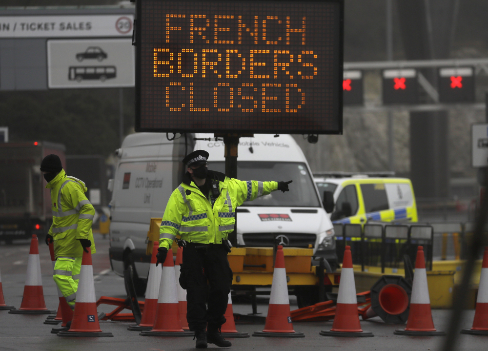 A police officer directs traffic at the entrance to the closed ferry terminal in Dover on Monday, after the Port of Dover was closed and access to the Eurotunnel terminal suspended. France banned all travel from the U.K. for 48 hours from midnight Sunday, including trucks carrying freight through the tunnel under the English Channel or from the port of Dover on England's south coast.