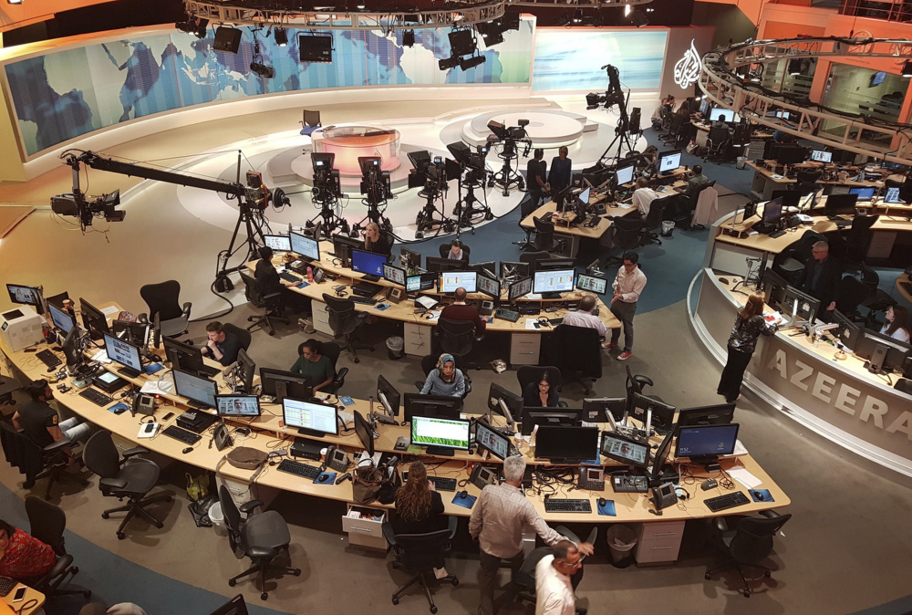 "Al-Jazeera staff work at their TV station in Doha, Qatar, in 2017. Citizen Lab at the University of Toronto tied the attacks ""with medium confidence"" to Emirati and Saudi governments."