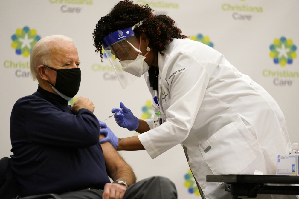 President-elect Joe Biden receives his first dose of the coronavirus vaccine at ChristianaCare Christiana Hospital in Newark, Del., Monday, Dec. 21, from nurse practitioner Tabe Mase.