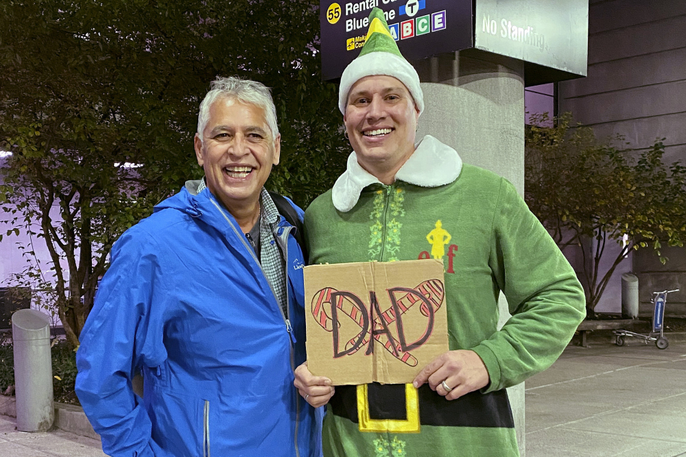 "Doug Henning, right, who was adopted as a baby, poses with his biological father after meeting face to face for the first time on Nov. 24 at Logan International Airport in Boston. Henning, of Eliot, Maine, wore a costume like the one actor Will Ferrell's character wore in the movie ""Elf"" and he broke into the same awkward song from the movie while meeting his father."