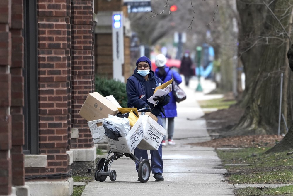 A postal worker delivers packages, boxes and letters Tuesday along her route in the Hyde Park neighborhood of Chicago.