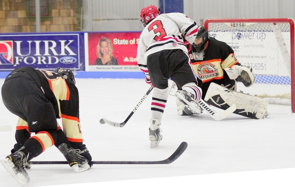 Cony's Dallas Clark, center, gets past Brunswick defenseman Tyler Sullivan, left, to shoot and score on Brunswick keeper Blake Alexander during a 2013 Eastern Class A quarterfinal game at the Bank of Maine Ice Vault in Hallowell. Brunswick topped Cony 3-2 in double overtime.