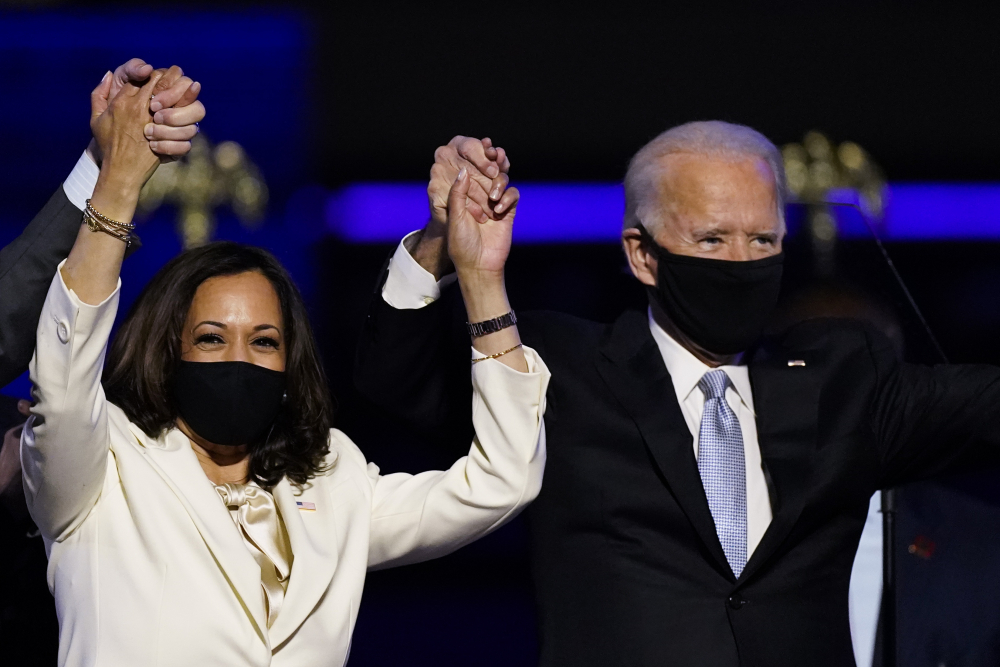 Vice President-elect Kamala Harris holds hands with President-elect Joe Biden after winning the election in November. Biden and Harris have been named Time magazine's Person of the Year.