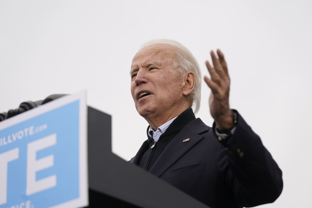 President-elect Joe Biden speaks at a drive-in rally for Georgia Democratic candidates for U.S. Senate Raphael Warnock and Jon Ossoff on Tuesday in Atlanta. Electors  formally cast votes on Monday affirming Biden's victory.